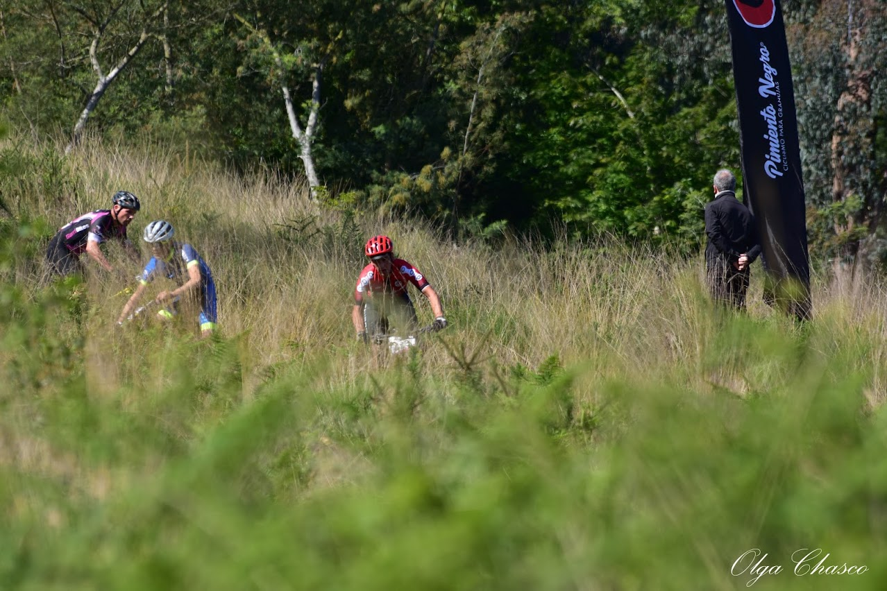 Tres ciclistas participan en la carrera Cannondale 2021 en medio de la naturaleza, bajo la mirada de un intendente